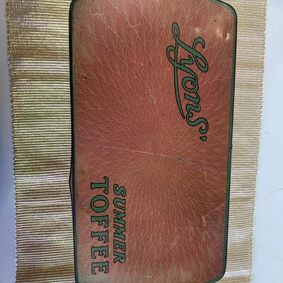 Lyons Summer toffee tin, in the colour orange, cream, green and black, used condition